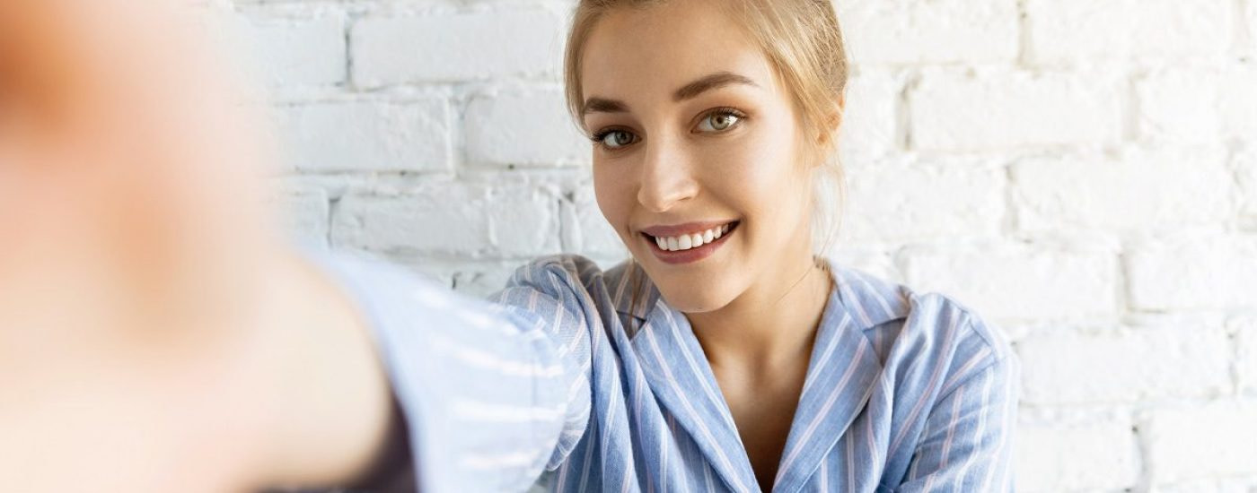 Portrait of attractive young woman in striped pyjamas making video call. Lovely model posing on white brick wall at home. Technology and good morning concept.