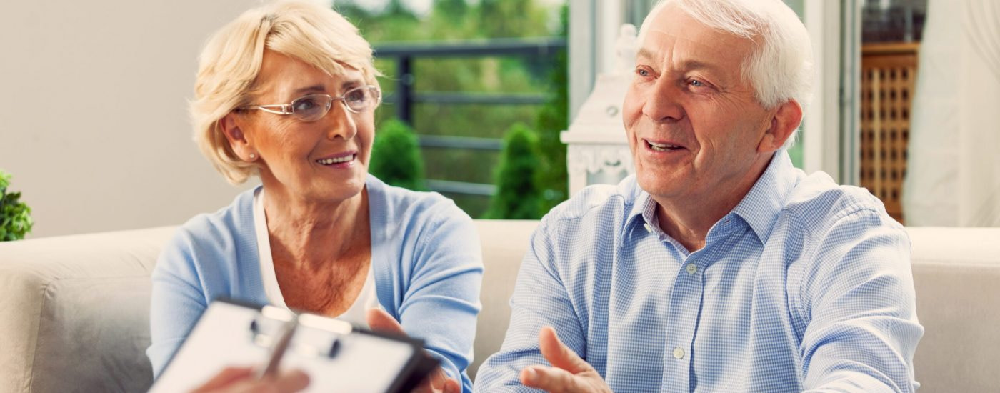 Cheerful senior couple having meeting with financial advisor or insurance agent at home.