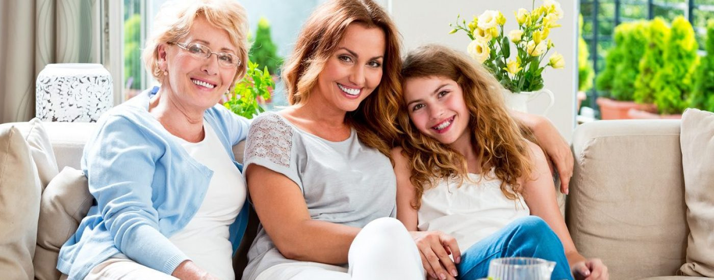 Portrait of mother, grandmother and daughter sitting on sofa at home and smiling at the camera.