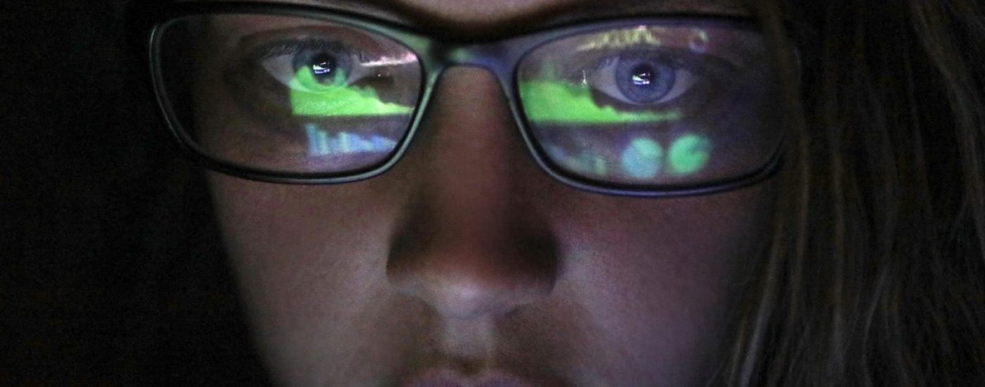 an Adult female looking at financial graphs on a laptop in a dark room with financial graphs reflected in his glasses.